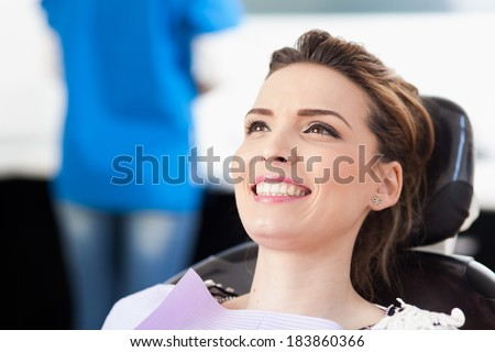 Closeup of a woman patient at the dentist waiting to be checked up with the woman doctor in the background
