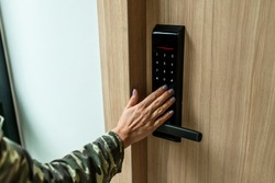 Closeup of a woman's finger entering password code on the smart digital touch screen keypad entry door lock in front of the room. Self Check-in, Modern security,Temporary codes.