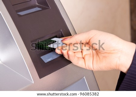 Closeup of a woman's had swiping a debit card through a scanner. Shallow depth of field.