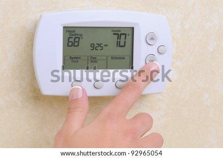 Closeup of a woman's hand setting the room temperature on a modern programmable thermostat.