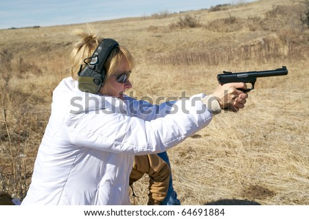Closeup of a woman taking target practice with a pistol at a shooting range.