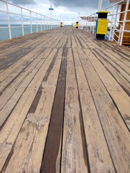 Closeup of a wooden pier with railings and ash bins and ladders coming to water. Wooden deck outside lake under overcast sky before the rain. Wooden pier for boats and yachts and jumps into water.