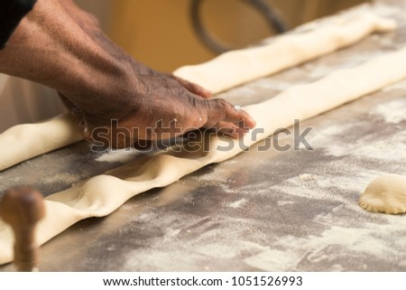closeup of a work table of a black old chef making filled pasta #1051526993