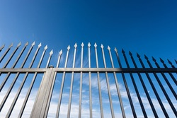 Closeup of a wrought iron gate with sharp points on blue sky with clouds and copy space.