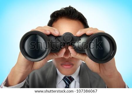Closeup of a young business man looking through binocular - stock photo
