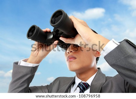 Closeup of a young business man looking through binocular in blue sky