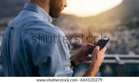 Closeup of a young businessman sending texts on a cellphone while standing on an office building balcony overlooking the city at dusk #664120279