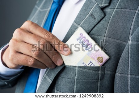 closeup of a young caucasian businessman, wearing an elegant gray suit, putting in or taking off some czech koruna banknotes in the pocket of his jacket