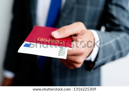 closeup of a young caucasian businessman, wearing an elegant gray suit, with his passport in his hand, with a 100 euros banknote in it