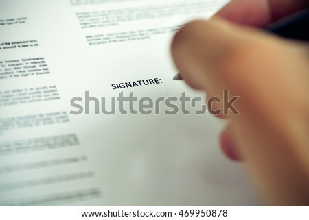 closeup of a young caucasian man about to sign a document with a pen under the word signature