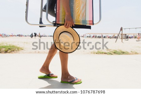 closeup of a young caucasian man carrying a beach chair and a straw hat in his hand, going or coming back from the beach