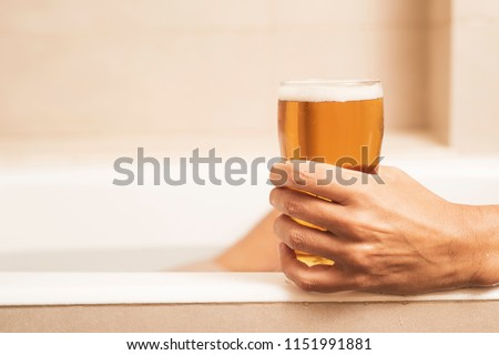 closeup of a young caucasian man drinking a refreshing beer while is taking a bath on the bathtub of a beige bathroom