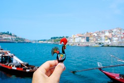 closeup of a young caucasian man holding a traditional Rooster of Barcelos, the emblem of Portugal, in Porto, at the Douro River with the Ribeira district on the right