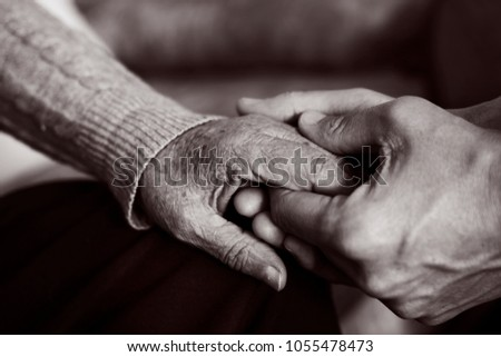 closeup of a young caucasian man holding the hand of an old caucasian woman with affection, in black and white