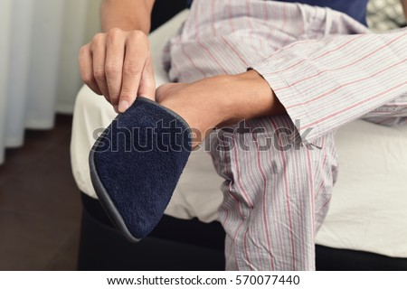 closeup of a young caucasian man in pajamas sitting on the edge of the bed putting on or off a pair of warm slippers