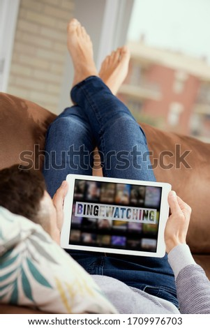 closeup of a young caucasian man, lying comfortably on a couch, watching his tablet, with the text bingewatching written in its screen Stock photo ©