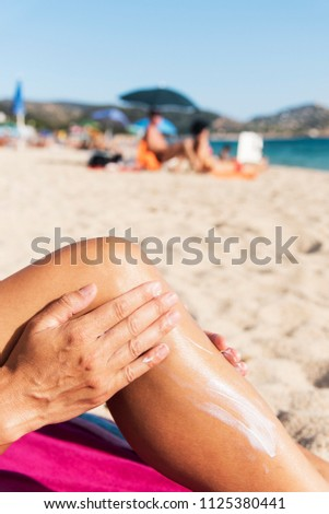 closeup of a young caucasian man on the beach applying sunscreen to his leg #1125380441