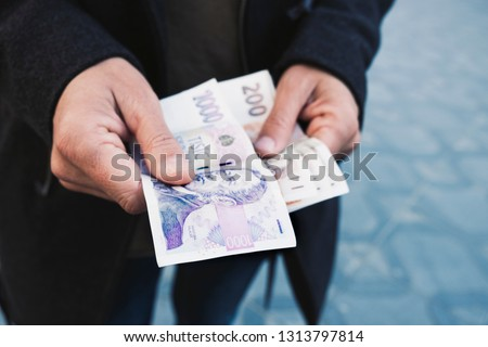 closeup of a young caucasian man on the street offering some czech koruna banknotes to the observer