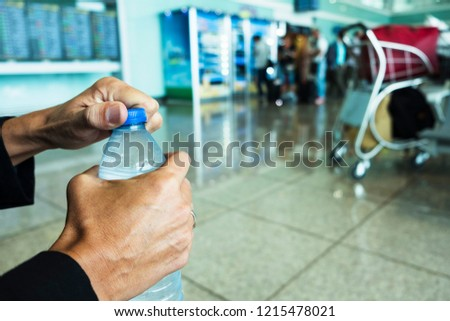 closeup of a young caucasian man opening a bottle of water at the waiting room of a train or bus station, or an airport