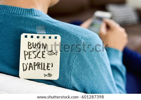 closeup of a young caucasian man seen from behind using his smartphone, with a note with the text buon pesce d aprile, happy april fools day in italian, attached with tape to his back