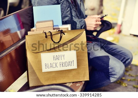 closeup of a young caucasian man sitting in a bench using his smartphone with some shopping bags, one of them with the text happy black friday written in it