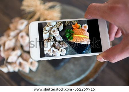 Closeup of a young caucasian man taking a picture with his smartphone of a plate with Japanese food sushi. Food Photography with smartphone.