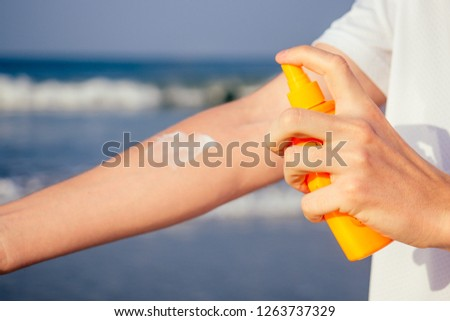 closeup of a young caucasian man wearing a white T-shirt applying sunscreen to his body against the sea ocean #1263737329