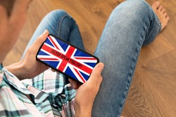 closeup of a young caucasian man, wearing casual clothes, sitting on a wooden floor, having his smartphone in his hands with the text do you speak English and the flag of UK in its screen
