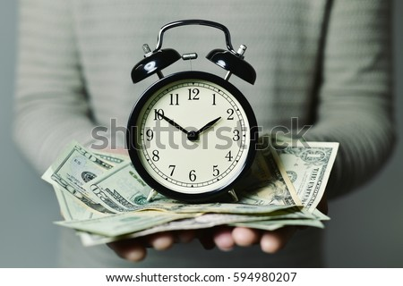 closeup of a young caucasian man with an alarm clock and many US dollar banknotes in his hands, depicting the idea that time is money