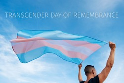 closeup of a young caucasian person, seen from behind, holding a transgender pride flag on the air and the text transgender day of remembrance on the sky