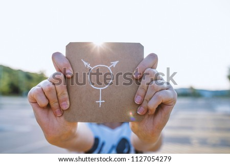 Closeup of a young Caucasian woman in the street showing a piece of paper with a transgender symbol drawn in it. The symbol of the transgender in hands on a cardboard plate #1127054279