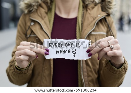 closeup of a young caucasian woman in the street showing a piece of paper with the text every day is march 8 written in it