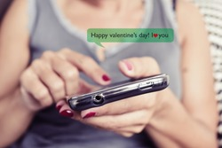 closeup of a young caucasian woman sending or reading a text message with a smartphone with the text Happy valentines day, I love you