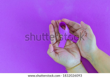 closeup of a young caucasian woman with a purple ribbon, for the awareness about the unacceptability of the violence against women. International Day for the Elimination of Violence Against Women.