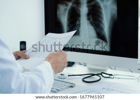 closeup of a young doctor man, wearing a white coat, sitting at his desk checking the results of a test and a chest radiograph in his computer Stock photo ©