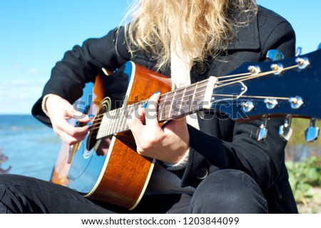 Closeup of a young female (no face pictured) playing an acoustic guitar, wearing mostly black.  #1203844099