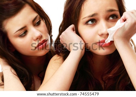 Closeup of a young girl crying and a friend calming her