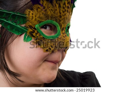 Closeup of a young girl playing dress-up and wearing a feather mask, isolated against a white background