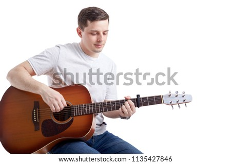 Closeup of a young man a playing spanish guitar. Isolated on a white background     #1135427846
