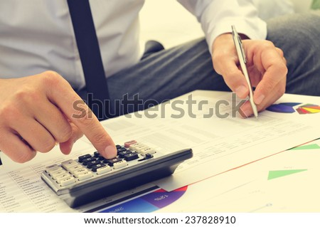 closeup of a young man checking accounts with a calculator