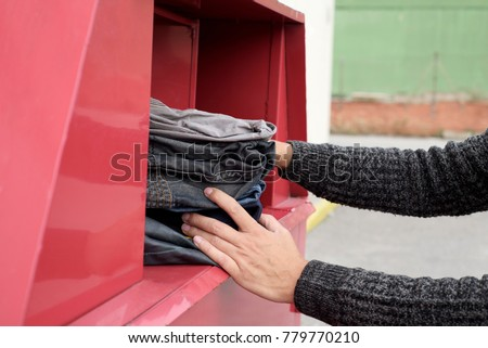 closeup of a young man depositing a pile of used clothes in a clothing bin in the street