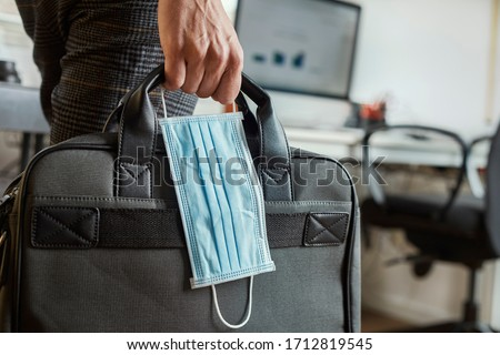 closeup of a young man in an office holding a briefcase and a surgical mask in his hand