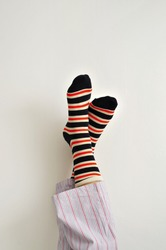 closeup of a young man in pajamas wearing colorful striped socks with his feet against the wall
