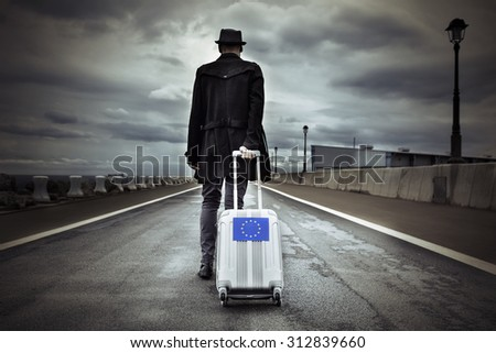 closeup of a young man seen from behind carrying his rolling suitcase with an European flag, with a dramatic effect