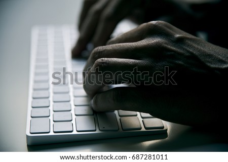 closeup of a young man typing in a computer keyboard in gloom, with a dramatic effect