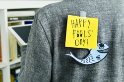 closeup of a young man with a paper fish and a note with the text happy fools day attached with tape to his back