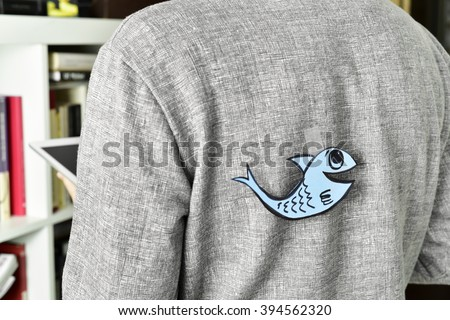 closeup of a young man with a paper fish attached with tape to his back, with a slight vignette added Photo stock ©