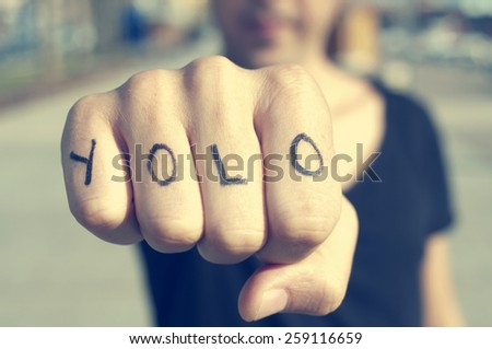 closeup of a young man with the word yolo, for you only live once, tattooed in his hand, with a filter effect