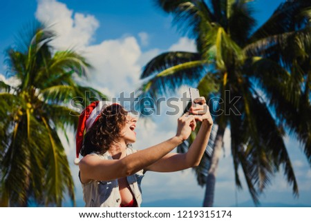 closeup of a young slim sexy girl in sunglasses red hat of Santa Claus on Christmas in New Year background of blue sky in summer sea palm in on holiday lifestyle with bikini big breasts smartphone #1219315174
