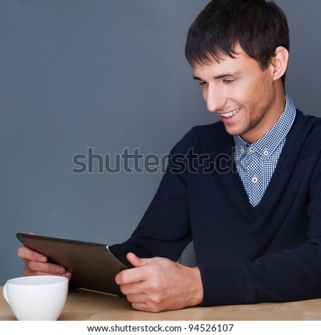 Closeup of a young smiling business man sitting at his office against gray wall and using his modern tablet pc to do his work